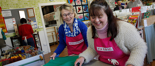 A person with disability and a disability support worker working in a fabric shop and smiling.
