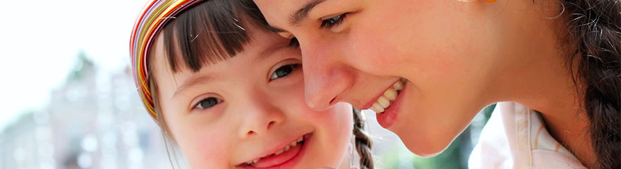 A woman and a young girl with disability smiling.