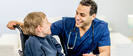 A person sitting in a wheelchair smiles at a young man who is kneeling and dressed in scrubs with a stethoscope around his neck