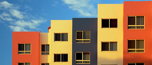 Apartment buildings against a blue sky.