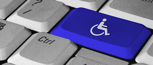 A blue keyboard key showing an icon of a person sitting on a wheelchair