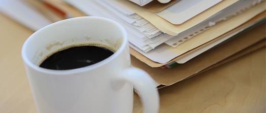 A close-up of a cup of black coffee in a white mug, sitting on a desk, with a stack of professional papers sitting on the desk out of focus behind the cup