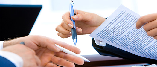 Close up of two peoples hands, one person is holding a pen and paper