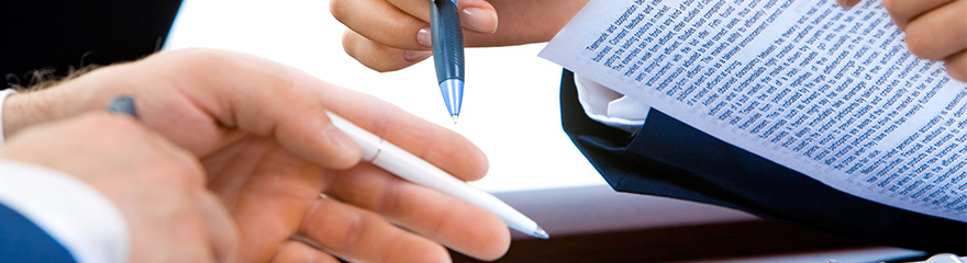 Two people's hands holding pens and a document.
