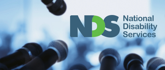 A row of microphones in front of blurry crowd and NDS logo