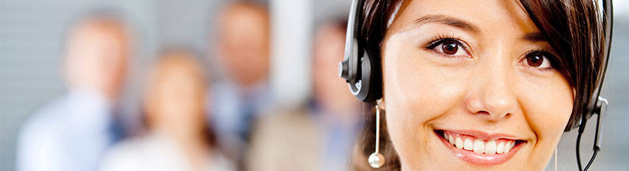 Woman working in a call centre with a headset and four colleagues standing in the background