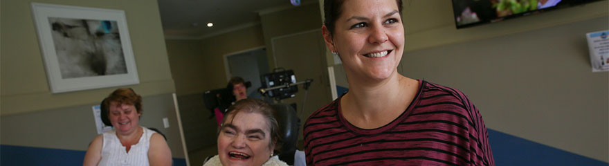 Image of a carer and two women in wheelchairs.