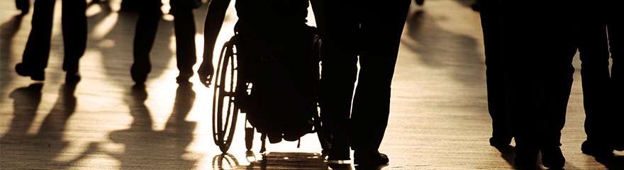 Silhouettes of someone seated in a wheelchair and people walking down a path