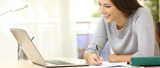 woman sitting at a laptop smiling
